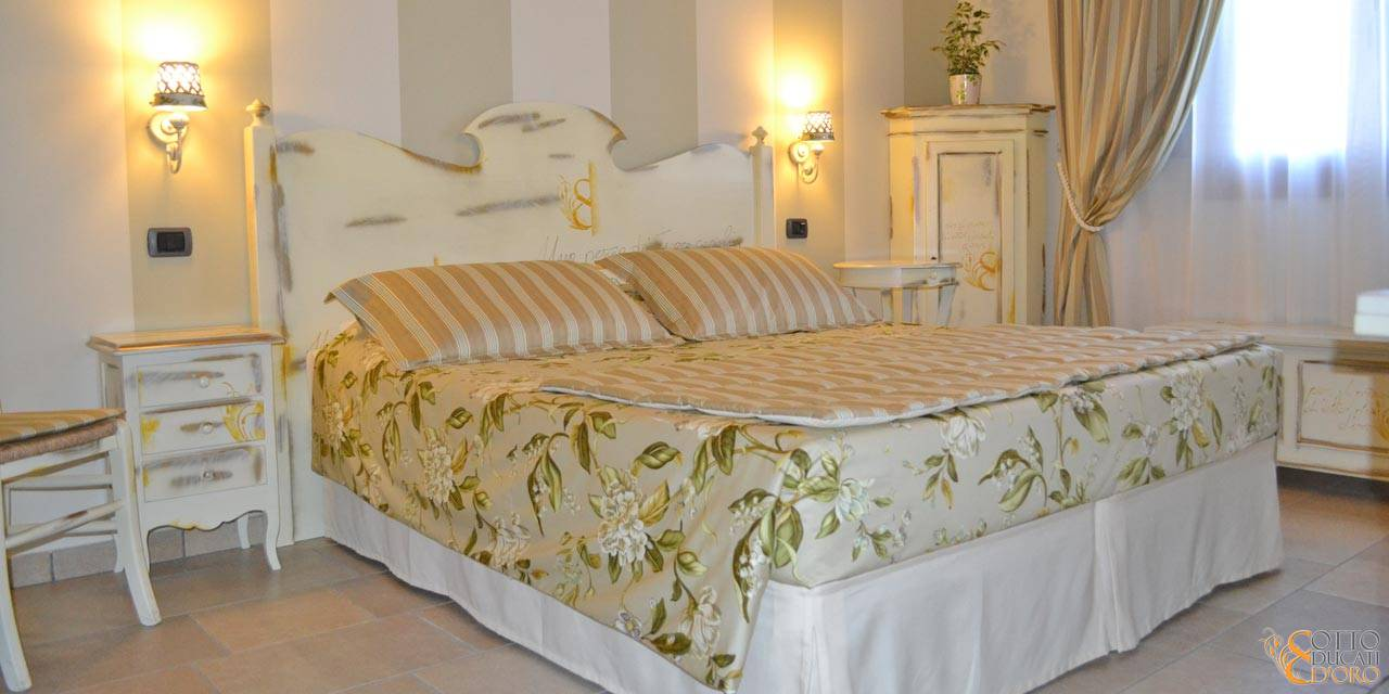 Provençal-style bedroom interiors with custom furniture at the Otto Ducati d'Oro country hotel and bed and breakfast