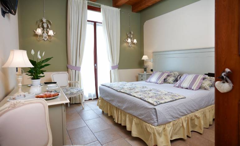 Romanzo: camera superior  decorata con colori pastello nelle sfumature del lilla e del verde